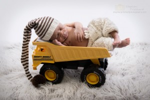 Newborn baby boy in toy dumper truck